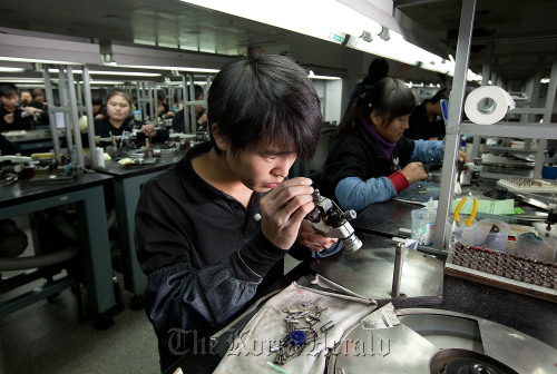 Workers polish diamonds in one of two rooms of polishing benches at the Guangzhou Mickey Weinstock & Co. (Bloomberg)