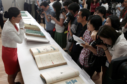 Reporters and photographers listen to Yoo Sae-rom, researcher at the National Museum of Korea, as she explains the significance of the five copies of ancient Korean royal books that were revealed to the media on Monday at the museum. (Kim Myung-sub/The Korea Herald)