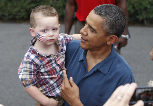President Barack Obama picks up a child as he greets military families at an Independence Day celebration on the South Lawn of the White House in Washington, Monday, July 4, 2011. (AP-Yonhap News)