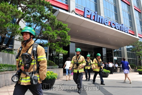 Firefighters leave TechnoMart in Seoul after finishing a survey Tuesday. Thousands of people were evacuated from the building following tremors there.(Park Hyun-koo/The Korea Herald)