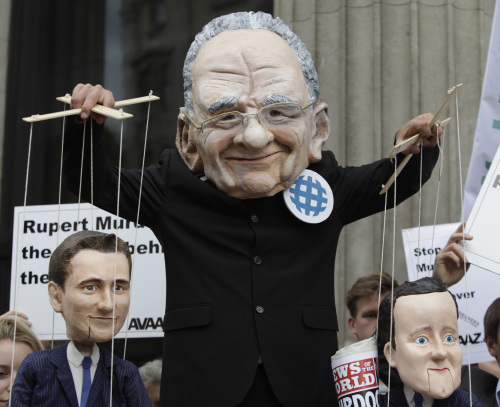 Rupert Murdoch depicted by a demonstrator (left) and Rebekah Brooks, chief executive of News International, which publishes the News of the World tabloid. (AP-Yonhap News)