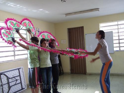 Mana Eugenia Olsen Agular (right) helps young Mexican women practice a Korean fan dance at the Merida Korean Language School. (Yonhap News)