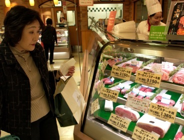 This file photo shows a Japanese woman browsing for beef in a food hall in Tokyo. (Bloomberg)