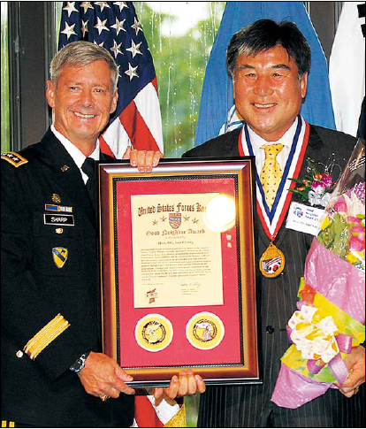 U.S. Forces Korea Commander Gen. Walter Sharp and Oh Seachang,mayor of Dongducheon City in Gyeonggi Province, pose for a photo during the 2011 Annual Good Neighbor Awards Ceremony at Yongsang Garrison in Seoul on Monday. (Yonhap News)