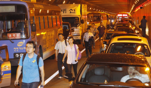 Passengers and drivers walk out of the tunnel. Yonhap News