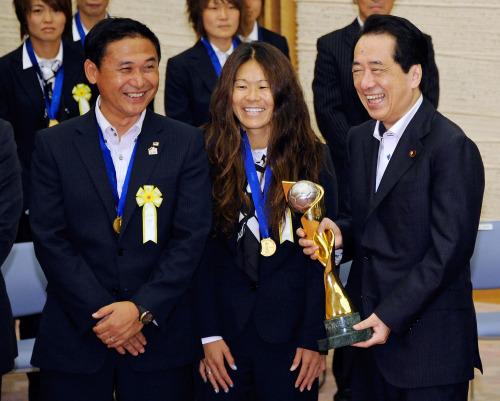 Japanese Prime Minister Naoto Kan (right) smiles as he holds the World Cup trophy with national soccer team player Homare Sawa (center) and head coach Norio Sasaki in Tokyo on Tuesday. (AP-Yonhap News)