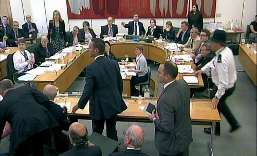In this image made from television, committee members and a policemen react after a protestor disrupted proceedings as James Murdoch, centre standing, Deputy Chief Operating Officer and Chairman and Chief Executive Officer, International News Corporation and Rupert Murdoch, seated, second left, Chairman and Chief Executive Officer, News Corporation gave evidence to a House of Commons Committe in London, Tuesday July 19, 2011, on the News of the World phone-hacking scandal.(AP-Yonhap News)