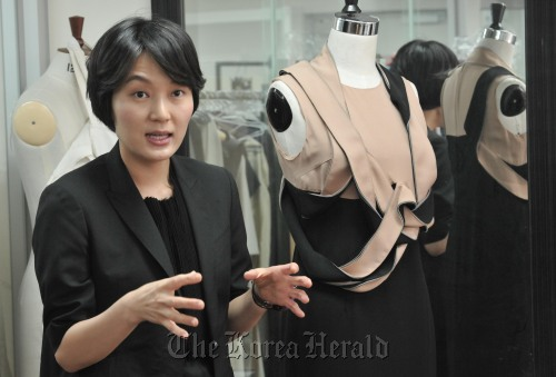 Leyii creative director Lee Seung-hee with one of her 2011 S/S collections. (Chung Hee-cho/The Korea Herald)