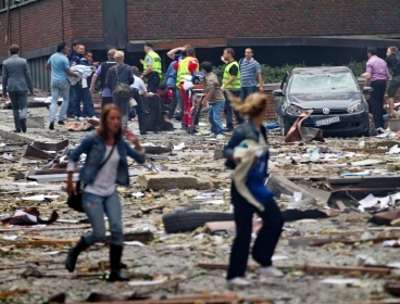 Two women are seen leaving as rescue workers arrive to help the injured following an explosion in Oslo, Norway Friday July 22, 2011. (AP)