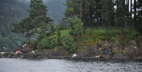 People are seen on the bank of the Utoeya island after a shooting took place at a meeting of the youth wing of Norway's ruling Labour Party, July 22, 2011. It was unclear whether the people were hiding or dead. (AP)