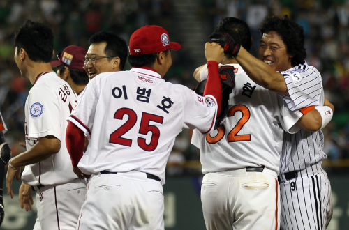 Lee Byung-kyu (right) celebrates with his teammates after hitting a single in the 10th inning on Saturday at Jamsil Stadium. (Yonhap News)