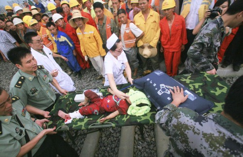 Rescuers carry an injured child to sent her to a hospital at the site where a high-speed train crash occurred in Wenzhou, east China's Zhejiang province, on Sunday. (AP-Yonhap News)