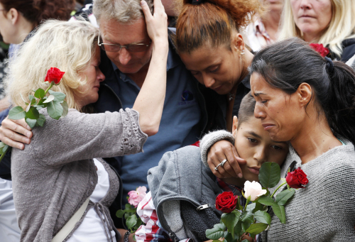 People comfort each other outside Oslo City Hall as they participate in a
