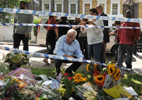 Mitch (crouching) and Janis Winehouse, (center right) father and mother of late British singer Amy Winehouse, look at flowers, pictures and messages left in tribute to their daughter near her house in north London, on Monday. (AFP-Yonhap News)