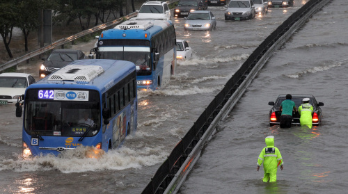 Vehicles wade through a water-logged road in Yeouido, Seoul, as heavy rains drenched the central part of the country on Wednesday. (Yonhap News)
