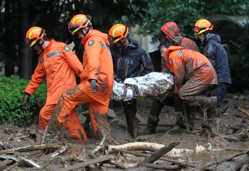 Rescue crew evacuate a resident on a stretcher from an area hit by a landslide in Chuncheon. (Yonhap News)
