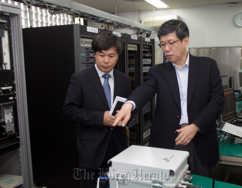 SK Telecom president Ha Sung-min (right) visits its supplier Contela's research and development room located at its office in Bundang earlier in May. (SKT)