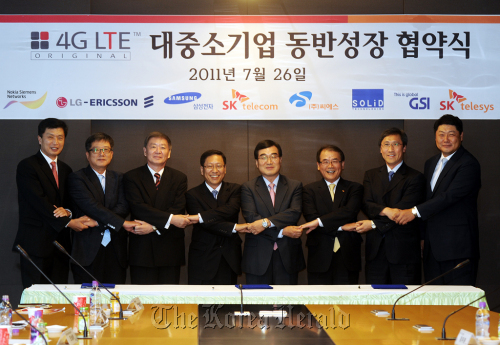 Kwon Hyok-sang (third from right), chief of network division at SK Telecom, poses with its seven partners after signing a mutual growth agreement involving the fourth generation network technology at the company's headquarters in Seoul on Tuesday. (SKT)