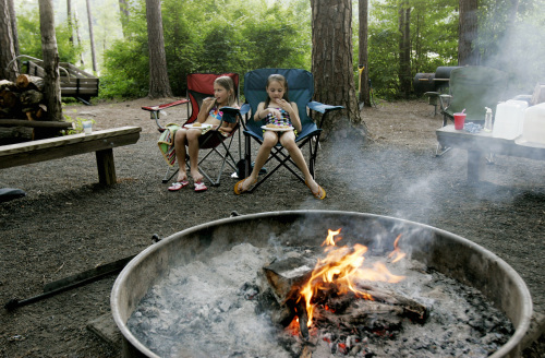 Nora McNabb, 8, left, and Rachel Laskowski, 9, eat dinner near the campfire during an annual multiple family camping trip at Falls Lake Shinleaf Campground, June 10, in Raleigh, NorthCarolina. (Raleigh News & Observer/MCT)