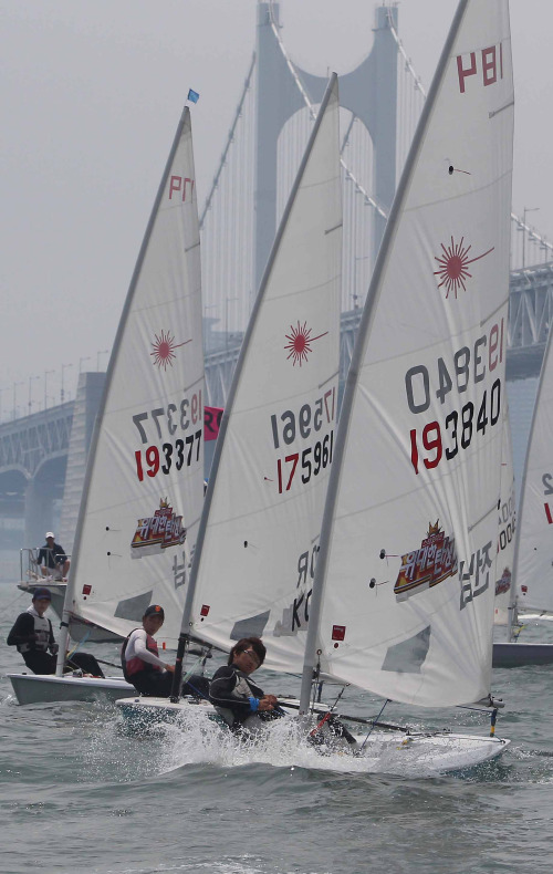 Sailors participate in a yacht competition off the coast of Busan on Sunday. (Yonhap News)