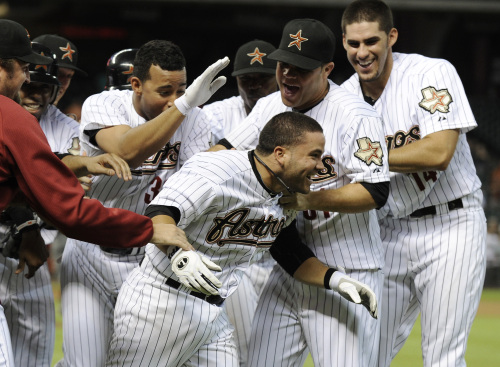 Houston Astros players mob Jose Altuve (center) after his game-winning hit against the Cincinnati Reds. (AP-Yonhap News)