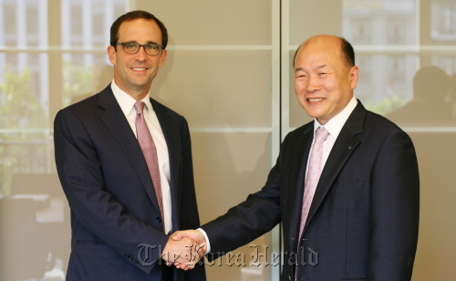 Kim Bong-whan (right), chief executive of AMOREPACIFIC Global Operations Ltd., shakes hands with Steven Hankin, managing director of Starwood Capital in Paris on Tuesday. (Amore Pacific)