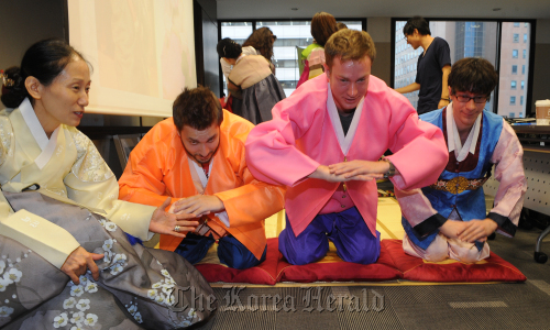 Foreign interns try to make a traditional Korean bow during a Korean culture event at the Korea Tourism Organization, Thursday. (Lee Sang-sub/The Korea Herald)