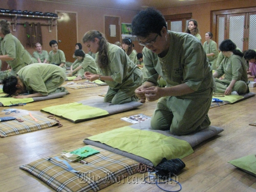 Lee Ho-lim (foreground) and other Templestay participants make rosaries on a recent morning at the Myogak Temple in Jongno, Seoul. (Rob York/The Korea Herald)