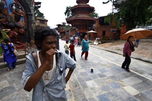 A man smokes near Basantapur Durbar Square in Katmandu, Nepal, Sunday. (AP-Yonhap News)
