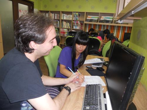 KKOOM volunteer Danny DiCrispino works with Sora, an Emmanuel middle school student. (KKOOM)
