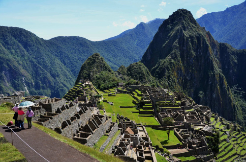 Sheltered by a parasol, these travelers take in the classic Machu Picchu view from just below the site's ancient guardhouse. (Christopher Reynolds/Los Angeles Times/MCT)