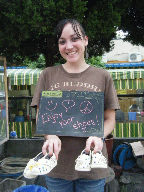 """A volunteer shows shoes she decorated at the Daegu """"Style Your Sole"""" event."""