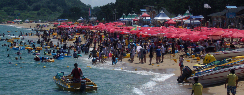 Vacationers swim and sunbathe at the provincial seaside town of Sokcho, 213 kilometers east of Seoul, on Aug. 21. Beaches on the country's eastern coast began shutting down on the same day. The Sokcho beach is scheduled to close on Aug. 29. (Yonhap News)