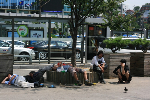 Homeless people sit outside Seoul Station on Tuesday. (kirsty Taylor)
