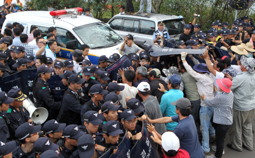 Residents of the Gangjeong village scuffle with police to stop a police van from carrying protest leader Kang Dong-kyun, arrested for obstructing the naval base construction in Seogwipo, Jeju Province, last Wednesday. (Yonhap News)