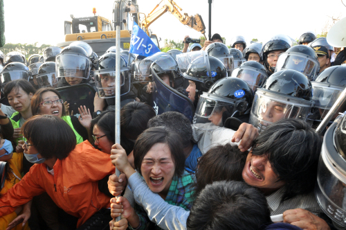 Police push protesters away from a naval base construction site on Jeju Island, Friday, to enable the military to install a fence before resuming construction. (Yonhap News)