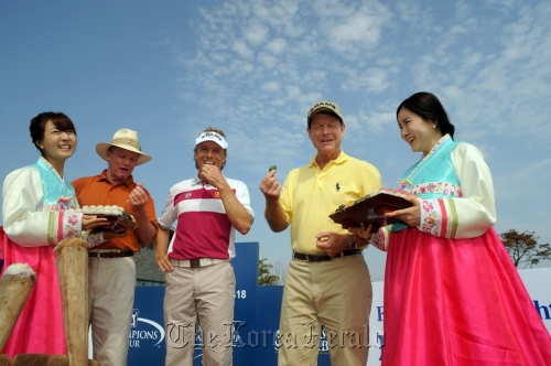 World golf hall of famer Tom Kite (second from left), Bernhard Langer (center) and eight-time major champion Tom Watson (second from right) try songpyeon at the Jack Nicklaus Golf Club in Incheon on Tuesday. (Songdo IBD Championship)