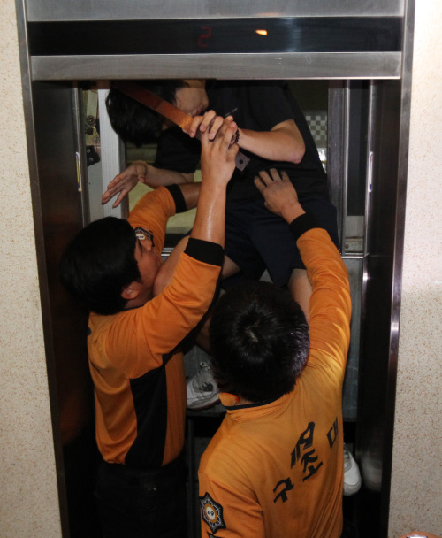 A man is taken out of an elevator by rescue workers after being trapped inside due to the power outage in Suwon on Thursday. (Yonhap News)
