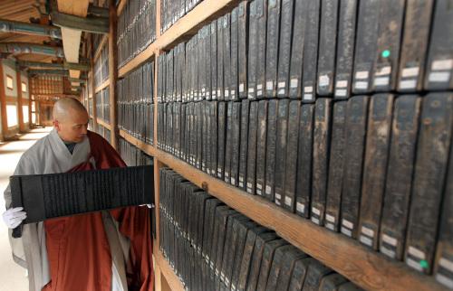 Seong-an, a monk at Haein Temple, shows a wooden block of the Tripitaka Koreana inside the Janggyeong Panjeon at the Haein Temple in Hapcheon, South Gyeongsang Province, Tuesday. (Yonhap News)