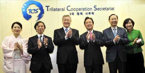 Officials from South Korea, Japan and China clap their hands in a ceremony to open the Trilateral Cooperative Secretariat in Seoul on Tuesday. From left are Counselor at the Japanese Embassy in Korea Matsukawa Rui, Japanese Ambassador to South Korea Masatoshi Muto, Foreign Minister Kim Sung-hwan, the secretariat's Secretary-General Shin Bong-kil, Chinese Ambassador to South Korea Zhang Xinsen and Director of the Office for Korean Peninsula of the Chinese Foreign Ministry Mao Ning. (Kim Myung-sub/The Korea Herald)