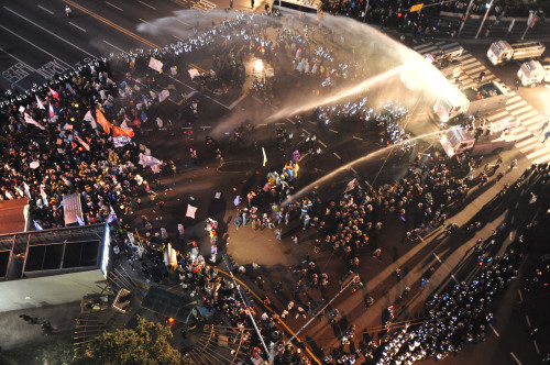 Police fire water cannons at demonstrators occupying a main road in downtown Busan on Saturday in protest of layoffs at Hanjin Heavy Industries and Construction Co. (Yonhap News)