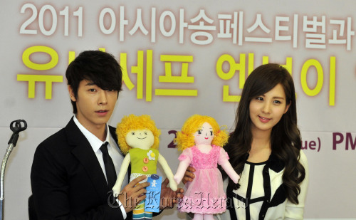 Donghae (left), a member of boy band Super Junior, and Seohyun of Girls' Generation hold UNICEF dolls that help raise funds for children in Africa at the Korean Committee for UNICEF in Seoul, Monday. (Kim Myung-sub/The Korea Herald)