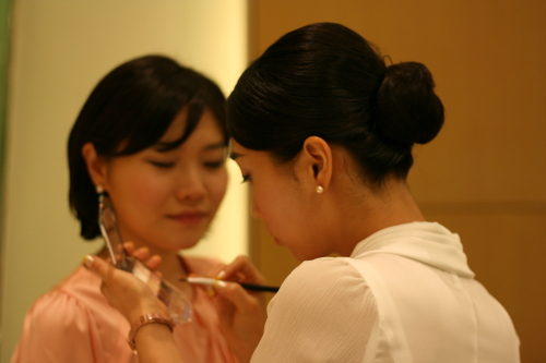 The long wait to be interviewed at the Qatar event leaves plenty of time to touch up makeup. (Hannah Stuart-Leach/The Korea Herald)