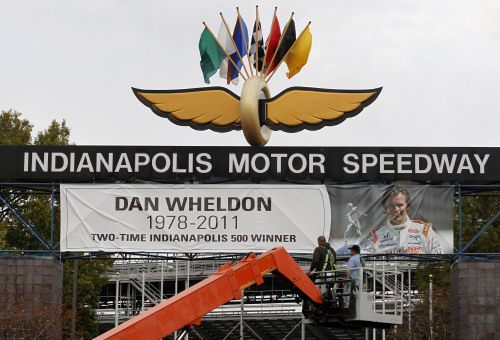 Workers install a banner to honor Dan Wheldon in Indianapolis on Monday. (AP-Yonhap News)