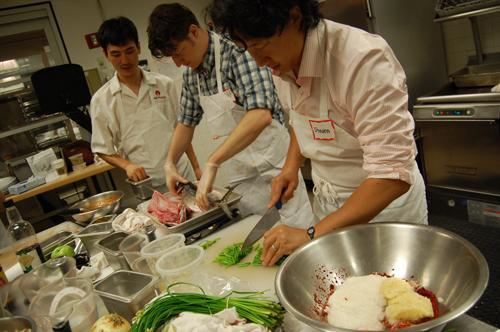 Chef Youngsun Lee (left) helps a student with salting mackerel, while Steve Ahn (right) prepares kimchi seasoning. (Yonhap News)