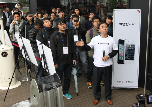 Customers line up at KT's flagship store in central Seoul to get iPhone 4S released Friday. (Yonhap)