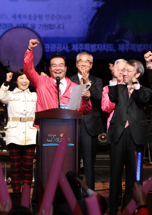 """Jeju Gov. Woo Keun-min gestures after announcing the listing of Jeju Island on """"New7Wonders"""" on Saturday morning at the Jeju Art Center. Chung Un-chan, chairman of the National Committee for Jeju New7Wonders of Nature (right), and Culture Minister Choe Kwang-sik (center, back row) also attended the event. (Yonhap News)"""