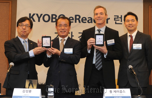 """Executive officials of Kyobo Book Center and Qualcomm unveil the """"Kyobo eReader,"""" the first e-book reader launched together by the two companies in Seoul on Tuesday. From left: Park Young-joon, director of the E-commerce department at Kyobo; Kyobo CEO Kim Seong-ryong; Qualcomm chairman Paul Jacobs; and Clarence Chui, senior vice president of Qualcomm MEMS Technologies. (Kyobo)"""