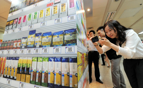 Customers scan the image of products using a Homeplus shopping app at Seolleung Station in Yeoksam-dong, southern Seoul. (Ahn Hoon/The Korea Herald)