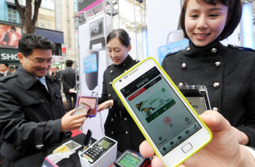A citizen taps a cell phone on a NFC chip reader during a mobile payment event held in Myeong-dong, central Seoul. (Ahn Hoon/The Korea Herald)